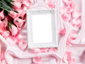 Empty photo frame with a bouquet sweet pink roses  petal on  soft pink silk fabric , romance and love card concept Royalty Free Stock Photo