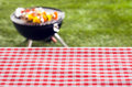 Empty picnic table background covered in a fresh country red and white checked cloth for your product placement or advertising Stock Photo
