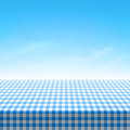 Empty picnic table covered with blue checkered tablecloth Royalty Free Stock Photo