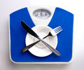 Empty plate for dieting concept white spoon and knife on blue scale Royalty Free Stock Photography