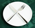 Empty plate fork and knife on green tablecloth Royalty Free Stock Photos