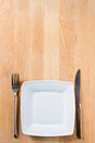 Empty plate with fork and knife table arrangement on wooden Royalty Free Stock Images