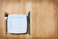 Empty plate with fork and knife table arrangement on wooden Stock Images