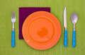 Empty plate with fork spoon and knife orange on a green tablecloth Stock Photo