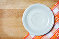 Empty plate over wooden background on tablecloth Stock Images