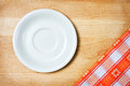 Empty plate on tablecloth over wooden background Royalty Free Stock Photos