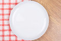 Empty plate on the wooden table with checkered tablecloth white Royalty Free Stock Image