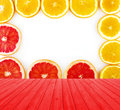 Empty red wooden deck table with fresh grapefruit and oranges rings set isolated on white background with copy space. Royalty Free Stock Photo