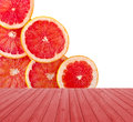 Empty red wooden deck table with fresh grapefruit rings set isolated on white background. Ready for product display montage Royalty Free Stock Photo