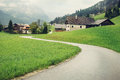 Empty road in Austria going to the alpine village Royalty Free Stock Photo