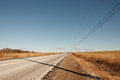 Empty road in the countryside with power lines and blue sky Stock Photography