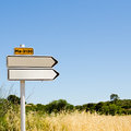 Empty road sign in the field yellow wheat grass over perfectly clear blue sky background pointing to right direction Royalty Free Stock Photo