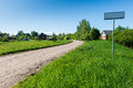Empty road with sign for village name Royalty Free Stock Photo