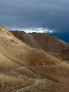 Empty rural road going through himalaya mountains high mountain landscape panorama with dramatic cloudy sky india ladakh Royalty Free Stock Image