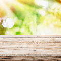 Empty rustic wooden table with golden sunlight rays of in a sunburst pattern over a blurred green country garden and bokeh Stock Photo