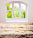 Empty scrubbed clean rustic wooden kitchen table under a pretty white domed window with cottage panes in a country ready Royalty Free Stock Image