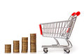 Empty shopping cart and stacks of coins Royalty Free Stock Photo