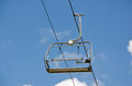An empty ski chair lift with blue sky Stock Images