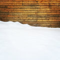 Empty space covered by snow near a wooden wall Royalty Free Stock Photo
