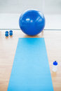 Empty sports hall with sport ball on background bright dumbbells and Royalty Free Stock Photo