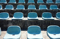 Empty stadium seats frontal view of light blue at a small or sports arena in a sunny summer day Stock Images