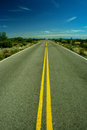 Empty straight line road travelling through a desert Stock Photo