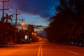 Empty street at early morning before dawn shrouded in mist illuminated by streets lights Royalty Free Stock Photo