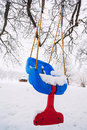 Empty swing chair in winter hanging from a tree Royalty Free Stock Photos