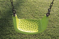 Empty swing set with green grass floor in background Royalty Free Stock Photos