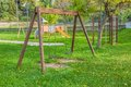 Empty swings at playground for child near children stairs slides equipment Royalty Free Stock Photo