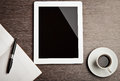 Empty tablet and a coffee on the desk Royalty Free Stock Photos