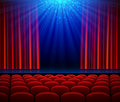 Empty theater stage with red opening curtain, spotlight and seats