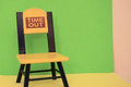 Empty time out chair blue yellow red green and pink walls and yellow floor background Stock Photo
