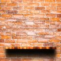 Empty top of wooden shelf with red brick wall. Royalty Free Stock Photo