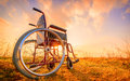 Empty wheelchair on the meadow at sunset Royalty Free Stock Photo