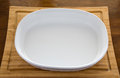 Empty White Casserole Dish on Wood Cutting Board Royalty Free Stock Photo