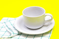 Empty white coffee or tea cup with towel on vibrant color backg the background Stock Images