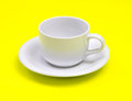 Empty white coffee or tea cup on vibrant yellow color background Royalty Free Stock Photo
