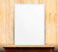 Empty white frame on wooden table at wood wall in background,Moc Royalty Free Stock Photo