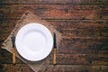Empty white plate with fork and knife on rustic wooden background Royalty Free Stock Photo