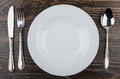 Empty white plate, knife, fork and spoon on table Royalty Free Stock Photo