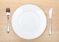 Empty white plate with silverware on wooden table Royalty Free Stock Photo