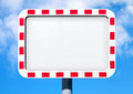 Empty white road sign with red striped frame above blue sky Stock Images