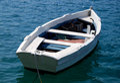 Empty White Row Boat on deep blue sea