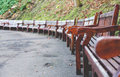 Empty wooden benches in round order in fall season in park Royalty Free Stock Photo