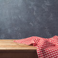 Empty wooden deck table with checked tablecloth over blackboard background Royalty Free Stock Photo