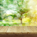 Empty wooden deck table with foliage bokeh background for product display montage. Spring or summer Royalty Free Stock Photo