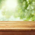 Empty wooden deck table foliage bokeh background ready product display montage Royalty Free Stock Photo
