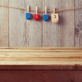 Empty wooden deck table with Hanukkah dreidel spinning top hanging on string Royalty Free Stock Photo