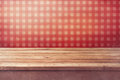 Empty wooden deck table over checked red wallpaper vintage kitchen interior ready for product montage Stock Photos